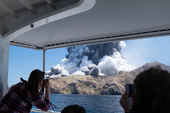 This handout photograph courtesy of Michael Schade shows the volcano on New Zealand's White Island spewing steam and ash moments after it erupted on December 9, 2019.