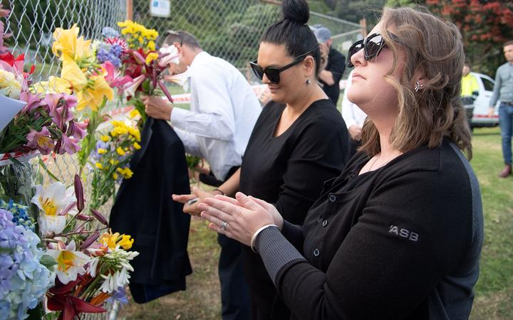 Bouquets of flowers are placed on the waterfront near White Island Tours base in Bay of Plenty,