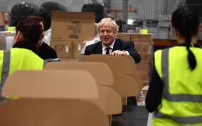 Britain's Prime Minister and Conservative party leader Boris Johnson helps out on the packing production line in a fulfilment centre for The Hut Group (THG) in Warrington, in north-west England on December 10, 2019,