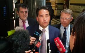 National leader Simon Bridges, flanked by National's Transport spokesperson Chris Bishop (L) and Finance and Infrastructure spokesperson Paul Goldsmith (R)