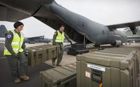 released by the Royal Australian Air Force on December 11, 2019 shows Flight Lieutenant Danielle Polgar (left) and Squadron Leader Shamus Shepherd  loading a C-130J Hercules prior to a mission to repatriate Australians at the Royal Airforce Base in Richmond.