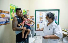 This picture released on December 5 by UNICEF Samoa shows nurse Fa'atafa Tavita (R) speaking with a family at the Apia Town Clinic in Samoa's capital city Apia.