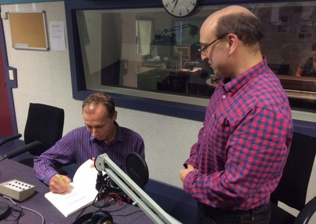 "David Farrar has his copy of ""Dirty Politics"" signed by author Nicky Hager in Radio New Zealand's Morning Report studio."
