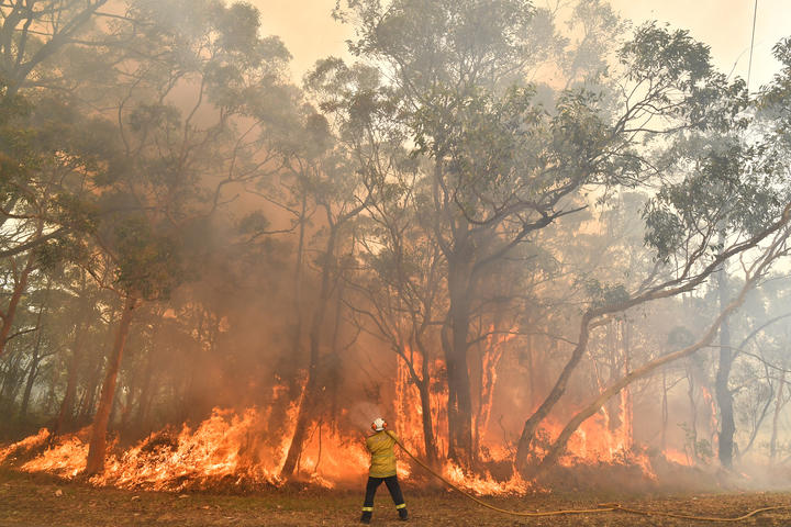 A firefighter conducts back-burning measures to secure residential areas from encroaching bushfires in the Central Coast, some 90-110km north of Sydney.