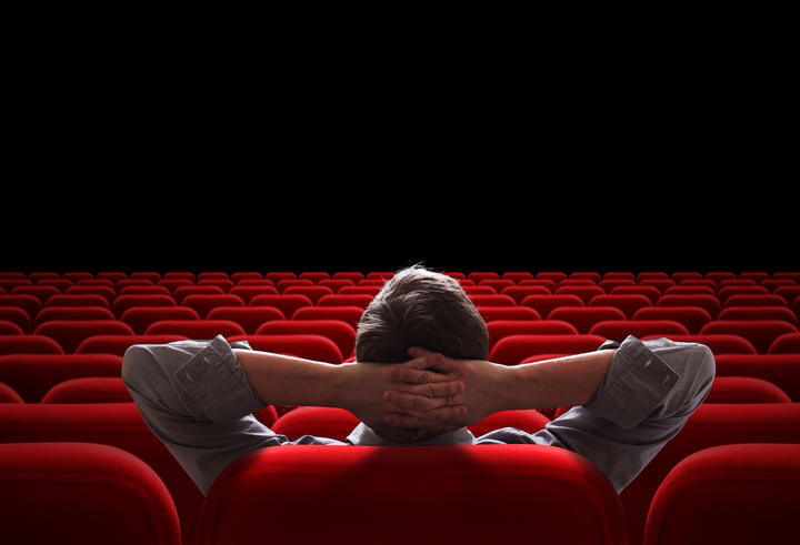 Image of happy male friends sitting in cinema watch film eating popcorn