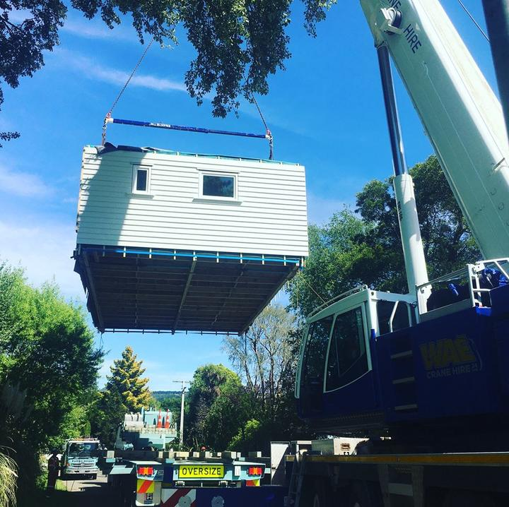 The basic structure of the climate safe house being lifted into place by a crane.