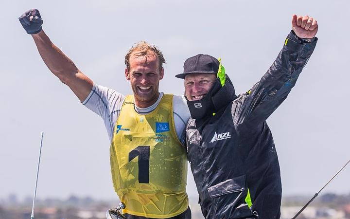 Josh Junior celebrates with coach Andrew Murdoch after becoming the first Kiwi to win the Finn World Champs.