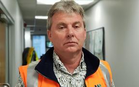 A man wearing an orange vest.