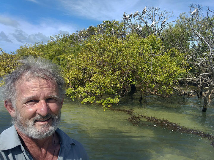 Kennedy with roosting red-footed boobies on Cosmoledo Atoll, in the Indian Ocean.