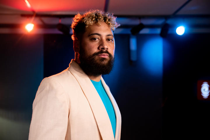 Noah Slee standing in the foreground wearing a white sports coat and azure shirt