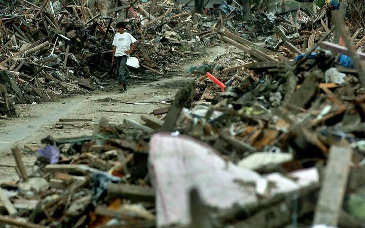 An Acehnese tsunami surviving young man walks along debris of houses in Banda Aceh, 29 January 2005.