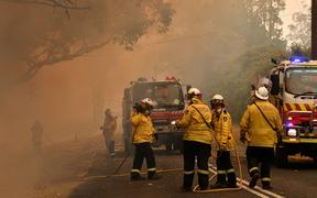 Firefighters conduct back-burning measures to secure residential areas from encroaching bushfires in the Central Coast, some 90-110 kilometres north of Sydney on December 10, 2019. -