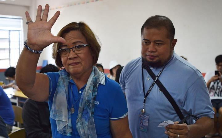 Detained opposition Senator Leila de Lima (L) waves to members of the media as she arrives to vote at a polling precinct in the city of Paranaque in suburban Manila on May 13, 2019. -
