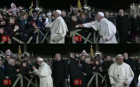 January 1, 2020 frame grabs taken from a handout video made available by Vatican Media shows a lady with her hands clasped as she watches Pope Francis arrive to celebrate New Year's Eve mass in Vatican City