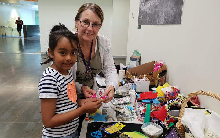 Sue Ollerton, sustainable living skills facilitator at Sustainable Papakura, with 7-year-old Aariya how to make Christmas decorations with rags and other waste that would other wise end up in landfill.