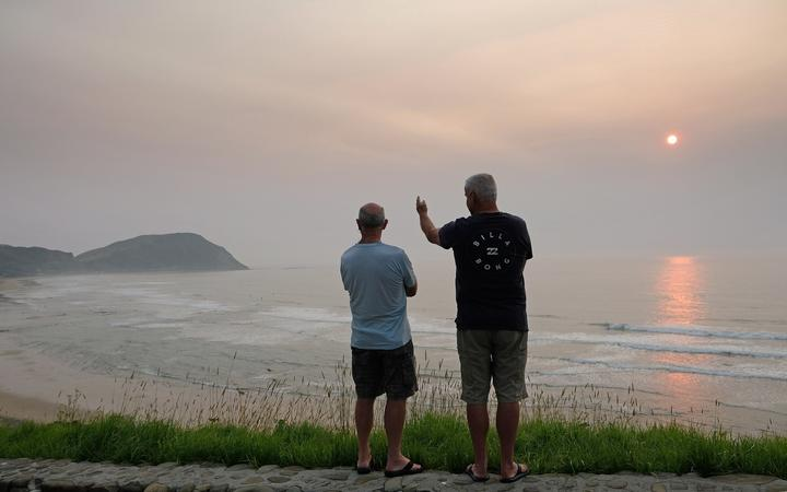 Two surfers look out across Makorori Beach near Gisborne where smoke haze from the Australia bushfires has cloaked the east coast in an fog-like haze turning the rising sun red.