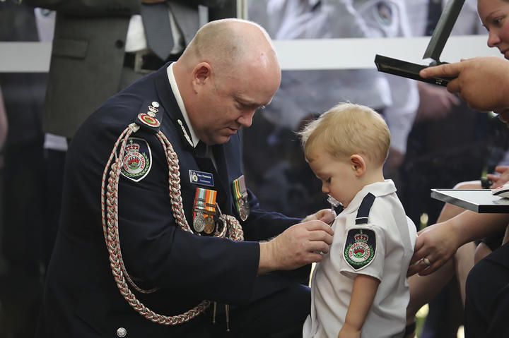 Australian Rural Fire Service Commissioner Shane Fitzsimmons pinning a medal on Geoffrey Keaton's son Harvey.