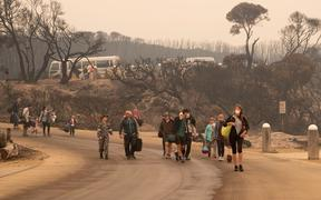 This handout photo taken on January 3, 2020 and released by the Royal Australian Navy shows people walking to a beach before being evacuated from Mallacoota, Victoria state to HMAS Choules, during bushfire relief efforts.