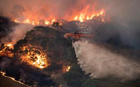 A handout photo taken and received on December 31, 2019 from the State Government of Victoria shows a helicopter fighting a bushfire near Bairnsdale in Victoria's East Gippsland region.