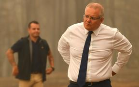 Australia's Prime Minister Scott Morrison (C) visits a resident's property in an area devastated by bushfires in Sarsfield, Victoria state on January 3, 2020.