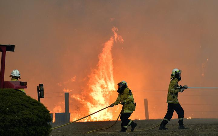This picture taken on December 31, 2019 shows firefighters working to stop a fire reach a house as bushfires hit the area around the town of Nowra in the Australian state of New South Wales. -