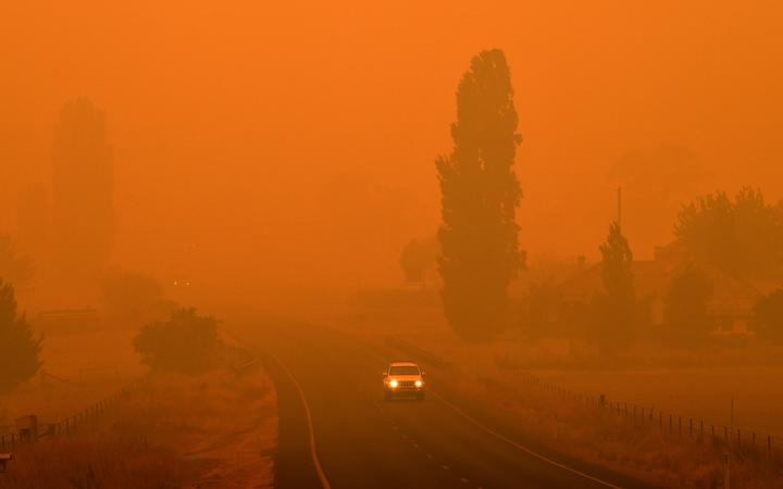 Residents commute on a road through thick smoke from bushfires in Bemboka, in Australia's New South Wales state on Sunday 5 January, 2020.