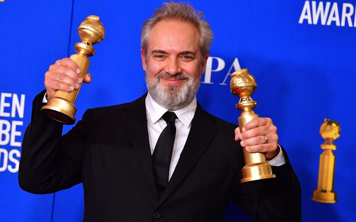 British film director Sam Mendes poses in the press room with the awards for Best Director - Motion Picture and best Best Motion Picture - Drama.