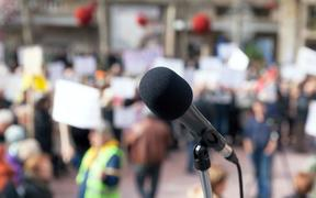 Microphone in focus against blurred protesters.