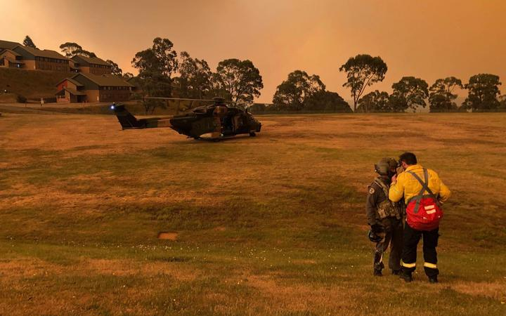 A Navy MRH-90 helicopter from 808 Squadron on a field at a residential area in the Omeo and Mt Hotham area of Victoria state, as part of evacuations during bushfire relief efforts.