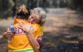 This photo taken on January 8, 2020 shows 64-year-old orchardist Stephenie Bailey (R) reacting as she describes the impact bushfires have had on her farm in Batlow, in Australia's New South Wales state.