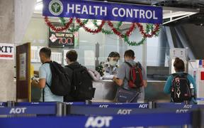 Foreign tourists queue at a health control counter at Suvarnabhumi airport, Thailand. The TAT is monitoring a viral outbreak in China's Hubei province.