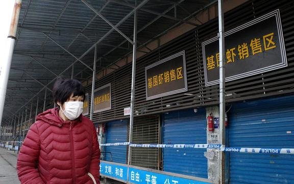 Une femme marche devant le marché de gros de fruits de mer fermé de Huanan, où les autorités sanitaires affirment qu'un homme décédé des suites d'une maladie respiratoire avait acheté des marchandises dans la ville de Wuhan.