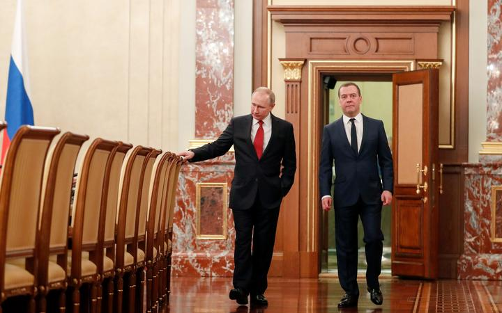 Russian President Vladimir Putin and Prime Minister Dmitry Medvedev walk before a meeting with members of the government in Moscow on January 15, 2020.