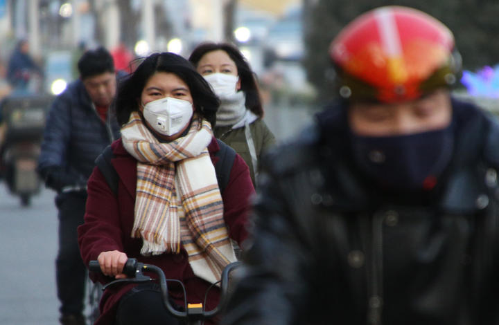 People wearing masks ride bycicles in Beijing, China on Jan. 21, 2020. Wuhan city announced that another patient had died due to the mysterious SARS-like virus on the previous day.