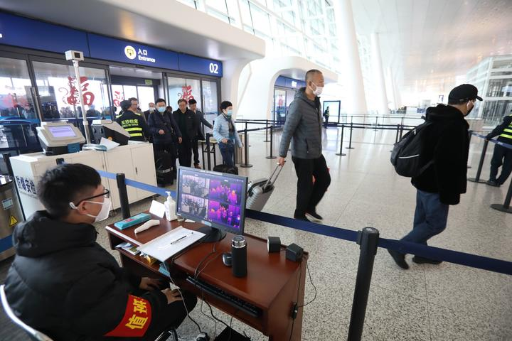 Staff members take passengers' body temperature at Tianhe International Airport in Wuhan, capital of central China's Hubei Province, Jan. 21, 2020.