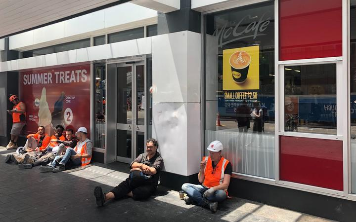 Construction workers wait for power to return outside the closed McDonald's cafe.
