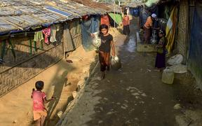A Rohingya refugee girl walks back to her makeshift house after collecting drinking water in Jamtoli refugee camp in Ukhia on 11 December 2019.