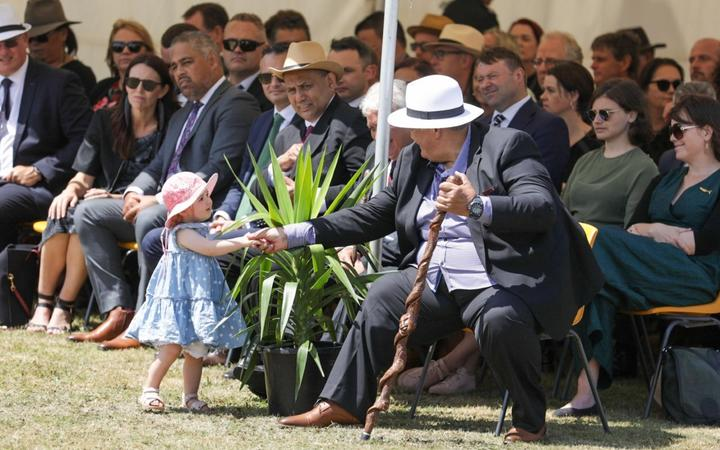 Prime Minister Jacinda Ardern's daughter Neve Te Aroha Gayford plays at the feet of those sitting near the pae.