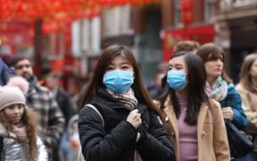 Women wear respirator masks during Chinese New Year Celebration in Chinatown in London, England on January 26, 2020.