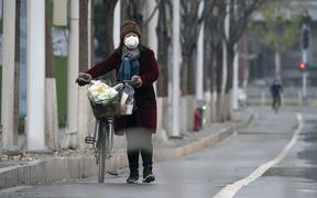 A woman wearing a mask walks along a street in Wuhan, central China's Hubei Province, on Jan. 26, 2020.