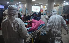 Medical staff wearing protective clothing coronavirus arrive with a patient at  Wuhan Red Cross Hospital.