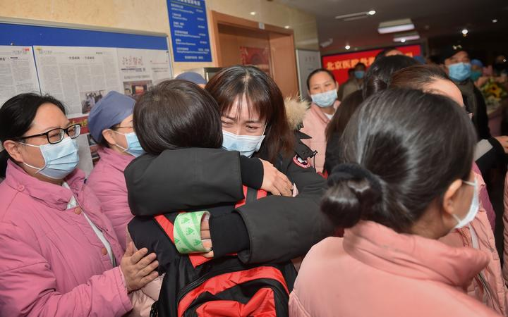A member of a 121-member medical team headed from Beijing to Wuhan is hugged by a colleague at Beijing Hospital.
