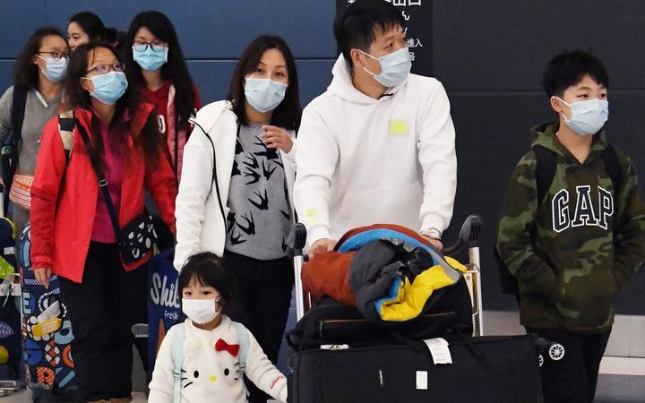 Passengers from China, wearing masks, arrive at Chubu Centrair International Airport in Tokoname City, Aichi Prefecture, middle of Japan, on January 27, 2020.