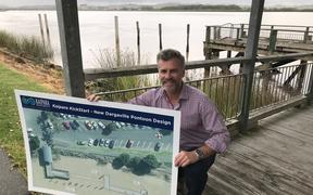 Kaipara District Council Mayor Jason Smith at Kaipara Harbour's Dargaville wharf with Dargaville pontoon rebuild design outline, the pontoon to be rebuilt where piles can be seen in photo background.