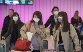 Passengers wear protective masks to protect against the spread of the Coronavirus as they arrive at the Los Angeles International Airport.