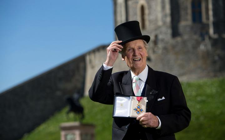 British radio and television presenter Nicholas Parsons poses with his Commander of the Order of the British Empire (CBE) medal given to him by Queen Elizabeth II at an Investiture ceremony at Windsor Castle in 2014.