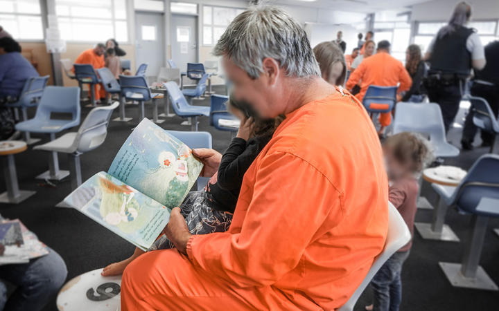 A dad reading to his child during a prison visit