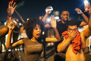 Demonstrators protesting over the killing  try to stand their ground despite being overcome by tear gas.