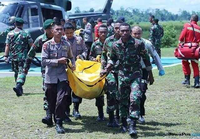 Indonesian soldiers and police carry the body of a colleague killed in Papua.