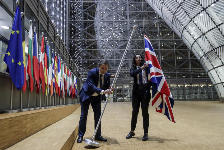 EU Council staff members remove the United Kingdom's flag from the European Council building in Brussels.